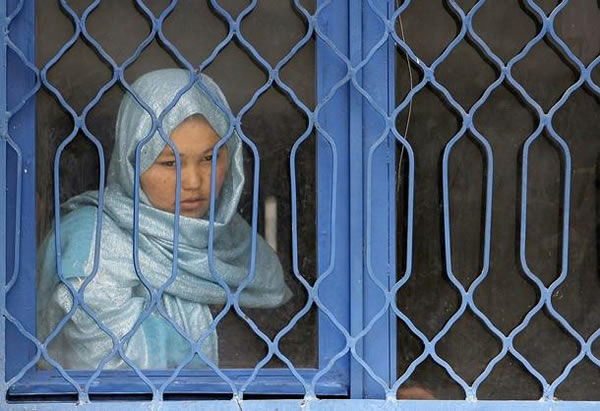 girl behind blue bars