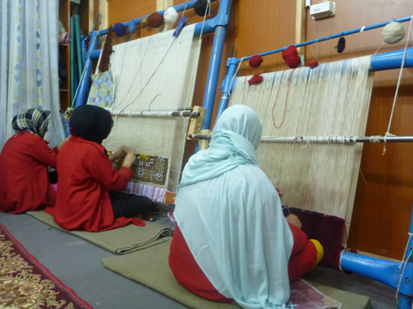 Women during carpet weaving in Herat province