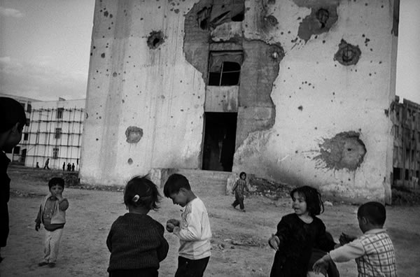 children-playing-by-shelled-building